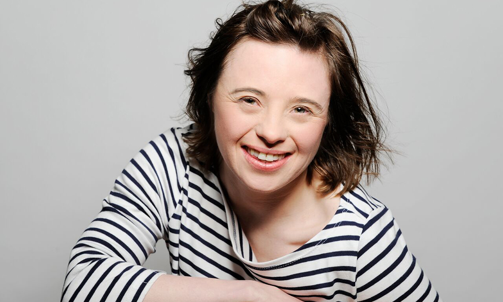British actor Sarah Gordy is dressed in a top with black and white stripes and is posing for the camera with a big smile