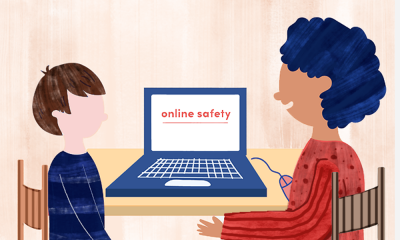 An older student explaining online safety to a younger child while a laptop is between them.