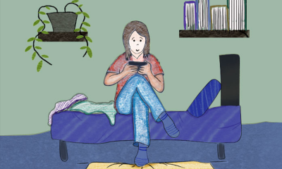 A girl sitting by herself on a bed, peering into her phone, in a dimly lit room.