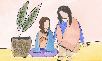In this illustration, there are two people, both wrapped in shawls. One of them seems younger and is sitting on the floor, next to a plant, with a cup in their hand. The other person seems to be older and is sitting on a pouf, with one hand on the younger person, as if to comfort them.