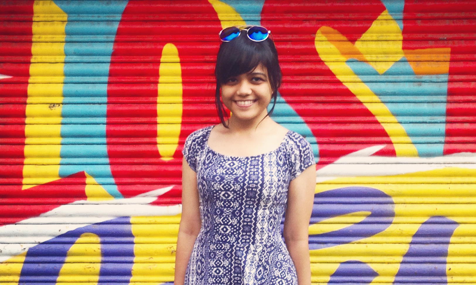 Pranita Kocharekar stands in front of a colourful garage door and smiles for the camera