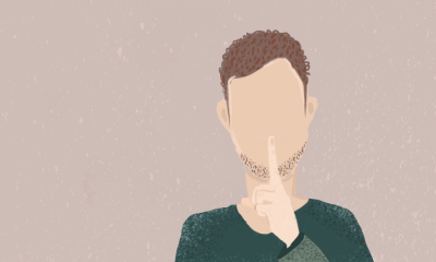 Illustration of a man wearing a green shirt, holding a finger up to silence himself.
