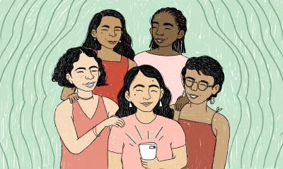 Five smiling women smiling and looking a cellphone