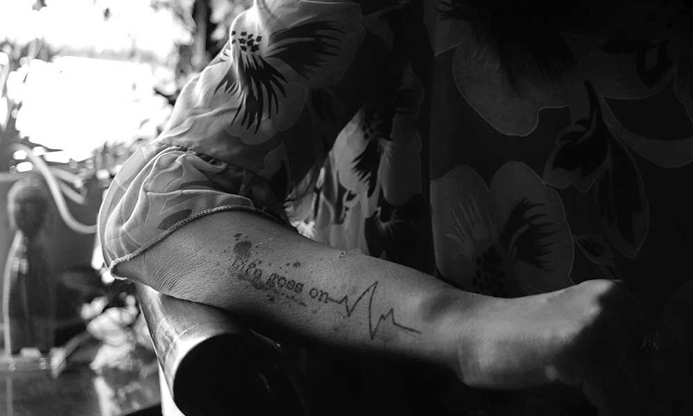 """A close-up black and white shot of Anju Chakraborty's tattoo that reads, """"life goes on"""""""