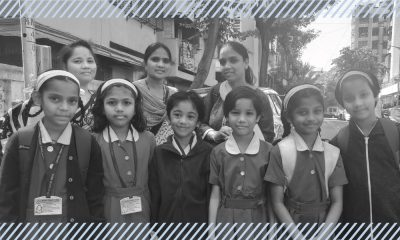 Female students of an Indian government school and their mothers smiling and staring at the camera.