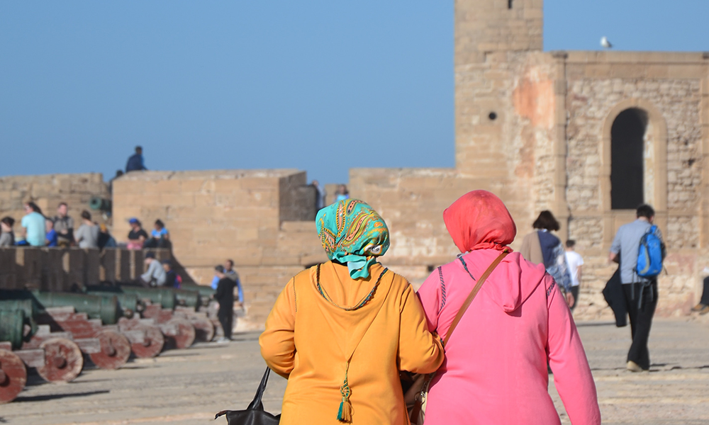 Two women in colorful jackets and headscarves walk arm in arm.