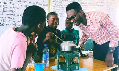 A photo of Henry Anumudu and his students conducting an experiment in the classroom.