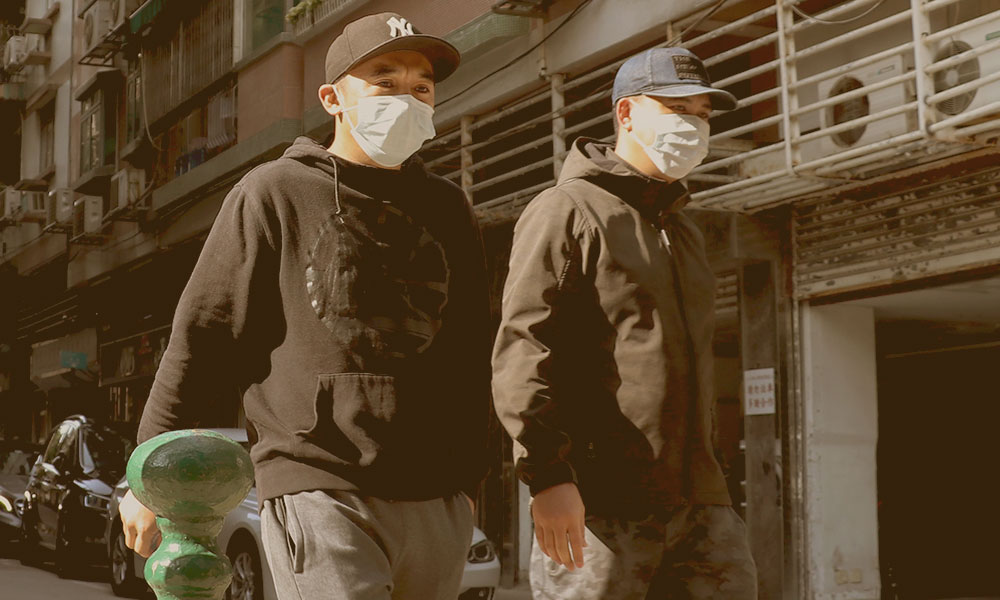 Two men walking on a street with white masks.