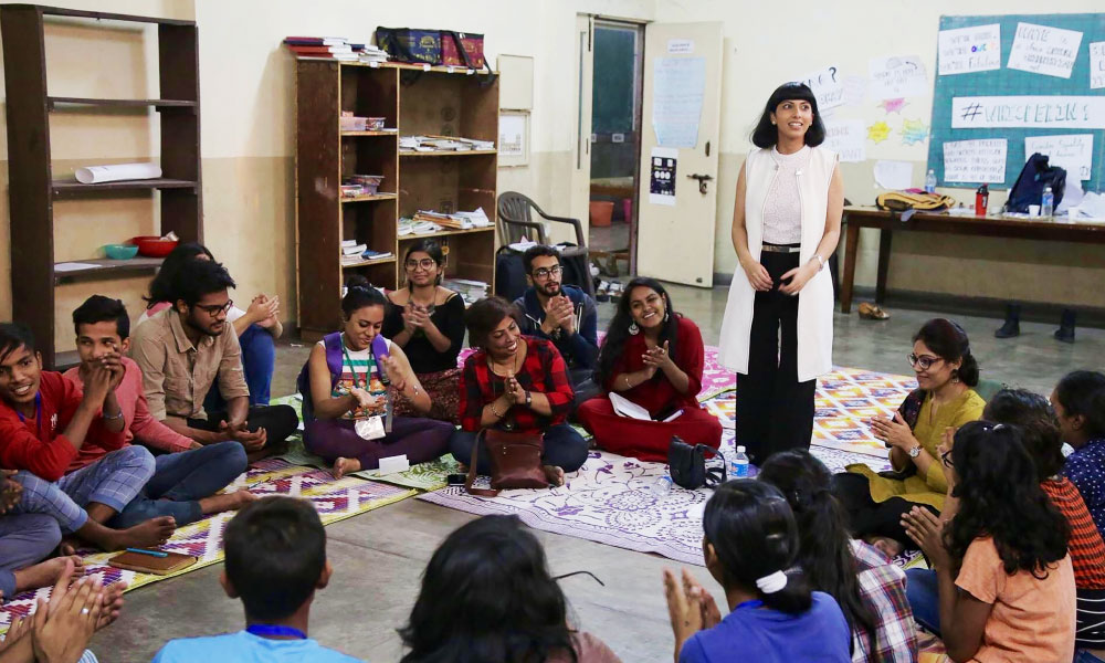 Divya Dureja conducts a gender sensitization workshop while parents are seated on the floor watching her.