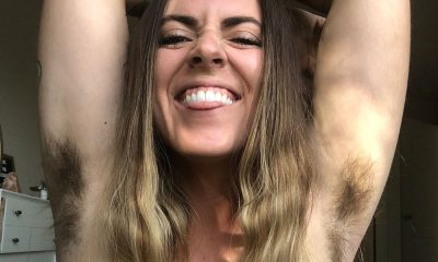 Brenna Pennly smiles at the camera while lifting her arms to show her unshaven underarms.
