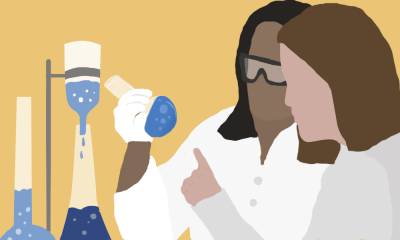 Two female scientists look at a glass beaker.
