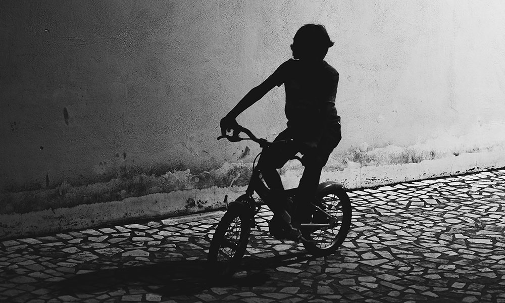 A dark image of a young child riding a bicycle.