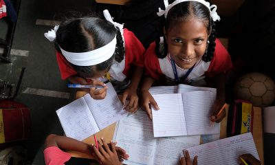 A close-up of two girls in pigtails and in red and white school uniforms studying together in class.
