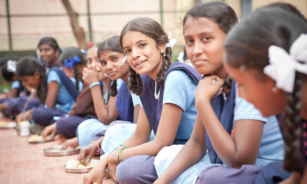 Pre-teen female students wearing white and blue salwaar kameez (a type of suit, worn especially by Asian women, with loose trousers and a long shirt) are sitting on the floor and eating chapatis.