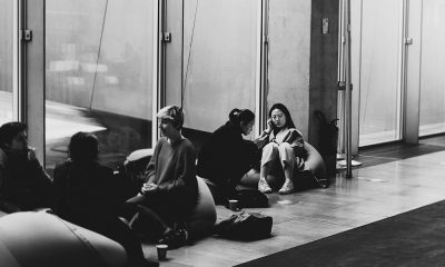 Three students sitting on bean bags pressed against a transparent door. The entire image is black and white, and the frame is focused on an Asian student speaking on her phone.