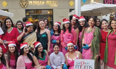 "Indian mothers in pink dresses and santa hats posing for a picture in front of a restaurant. One of them is holding a placard saying, ""Gurgaon Moms""."