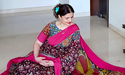 Vaishali Joshi sitting on the floor, looking at the drape of her saree.