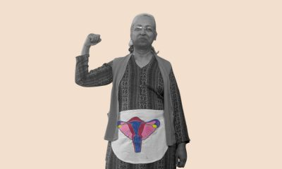 An old women, flexing her right arm, while wearing an apron around her waist diagramming the female reproductive system.