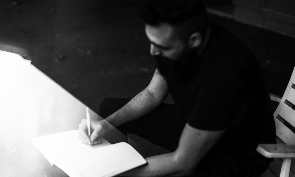 A black and white image of a bearded man writing in a diary.