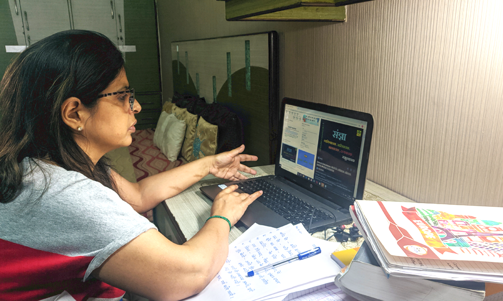 An Indian teacher working on a laptop in her home room. There's a stack of papers next to her, with a pen on top. She's wearing a grey t shirt and black glasses.