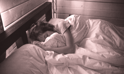 A woman lies in bed with her face buried in the sheets.