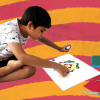 Madhav Kalra, a child on the autism spectrum is colouring on a paper. The background has an alternate curve pattern.
