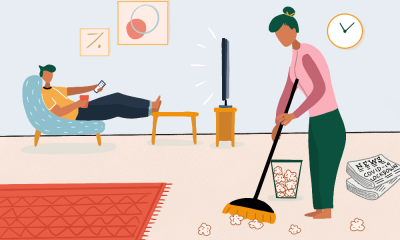An illustration where a woman cleans the floor in the foreground, as her husband sits on a chair with a drink in his hand, and watches TV.