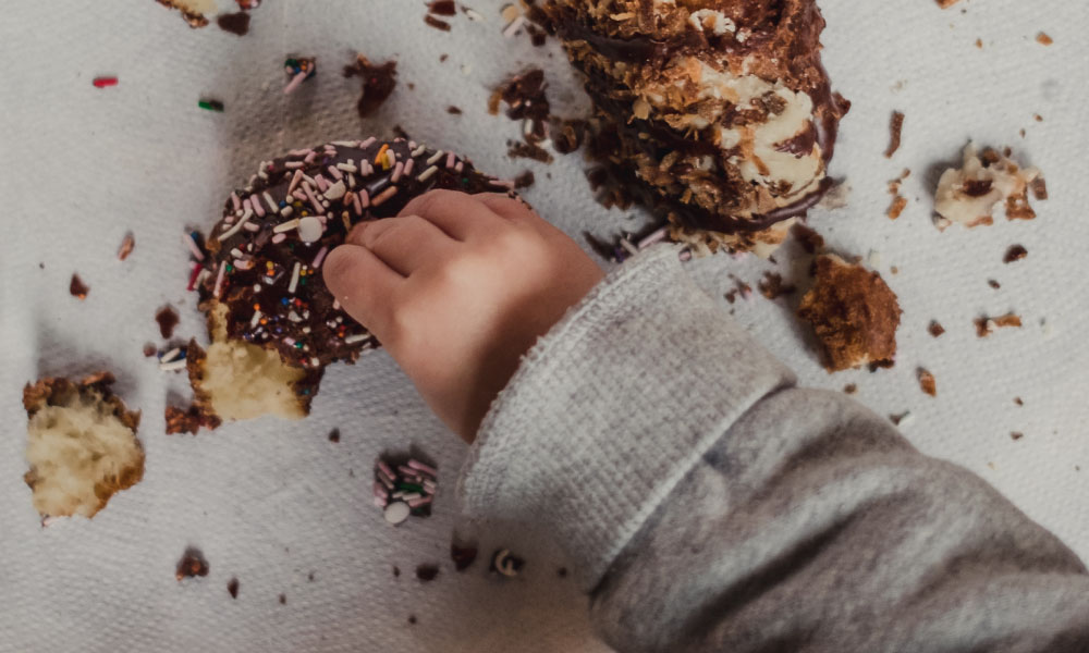 A child's hand smashes donuts