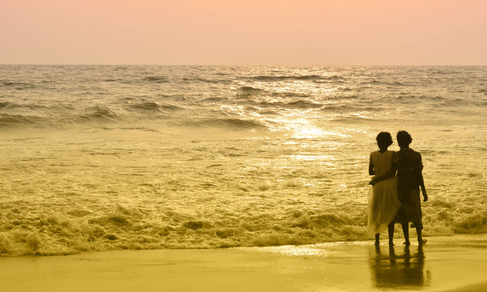 Two women hold each other while standing on the seashore.