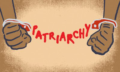 Two hands bound together with handcuffs reading Patriarchy