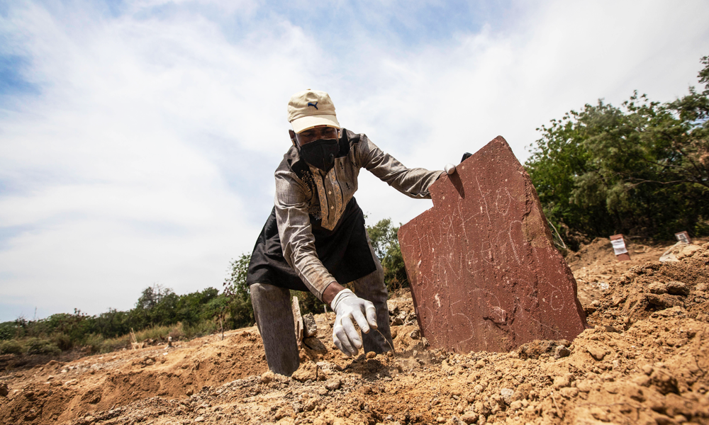 A grave digger is shoving a rustic tomdstone in the soil. He's wearing a snapback cap and silicon gloves.