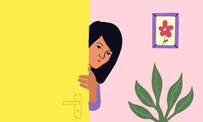 A girl peeping from behind a yellow door. There is a photo frame with a picture of a flower and a plant in the frame.