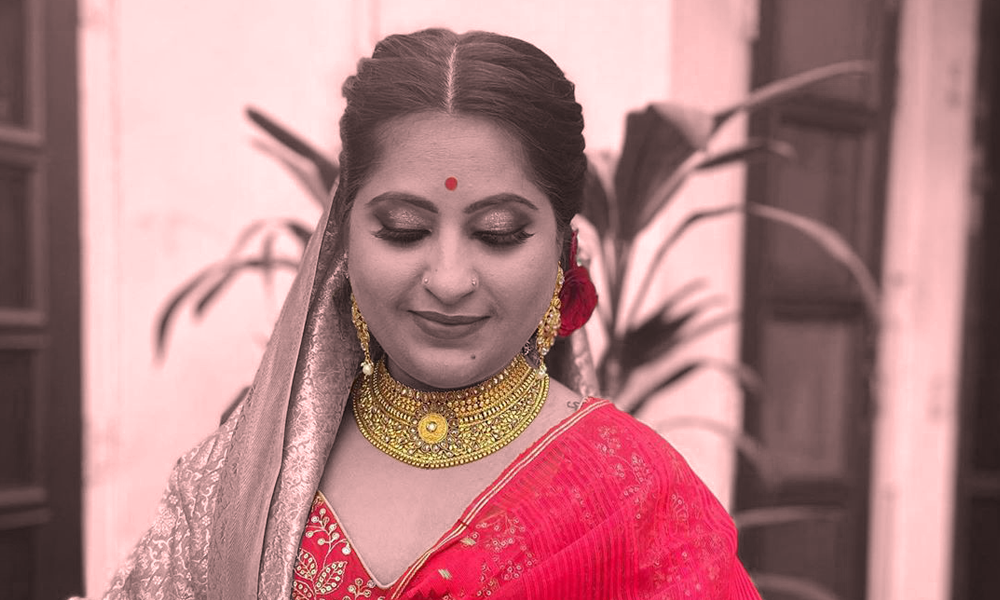 Close-up of an Indian bride, looking on the floor. she's wearing a red saree and gold jewelry.