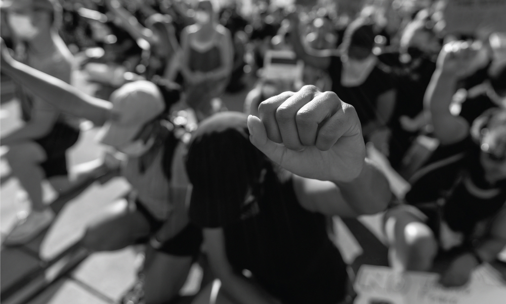 an image of people kneeling with their fists in the air