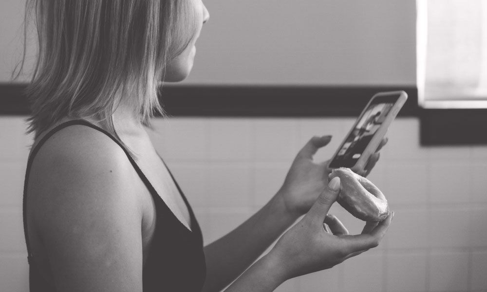 Image of a girl holding a bagel in one hand and a phone in the other.