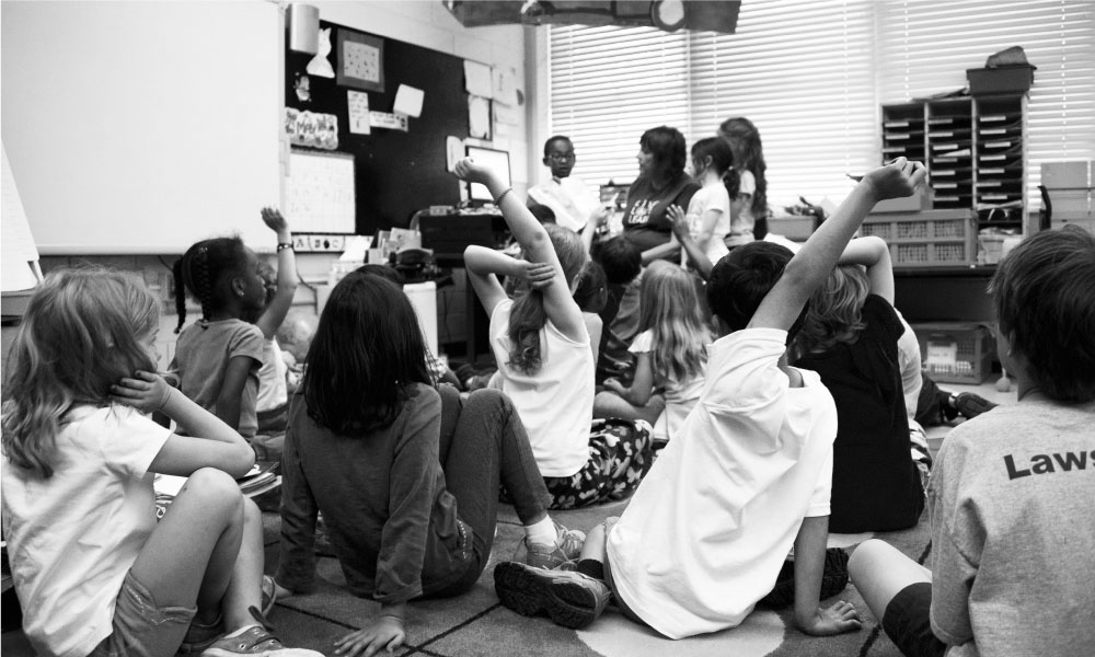 A black and white image of students raising hands in a class.