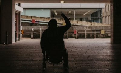 a silhouette of a black man on a wheelchair with his arm up in the air