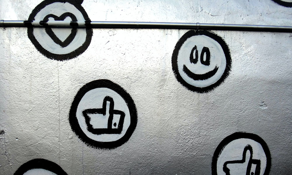 Positive symbols used to react to social media posts in black and white. There is the heart symbol, the smiling face symbol and the thumbs up symbol.