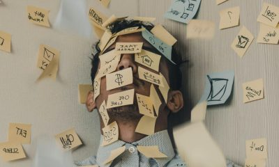 An Indian male seeming stressed, with face covered with sticky notes.