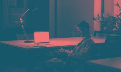A man sitting in a dark office alone.