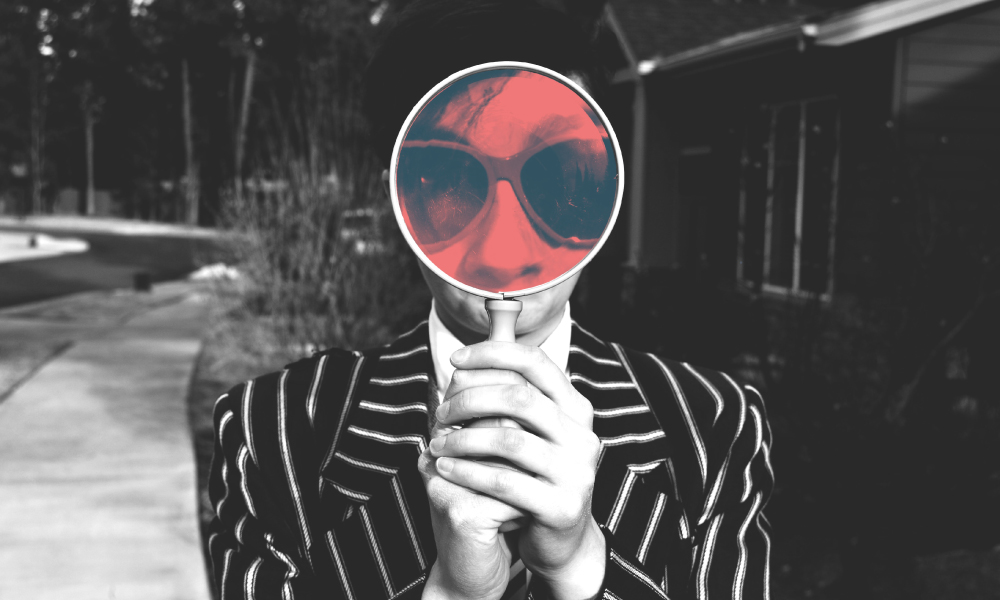 An image of a man holding a magnifying glass. The image is black and white and the area of the man's face behind the magnifying glass has a pink hue.
