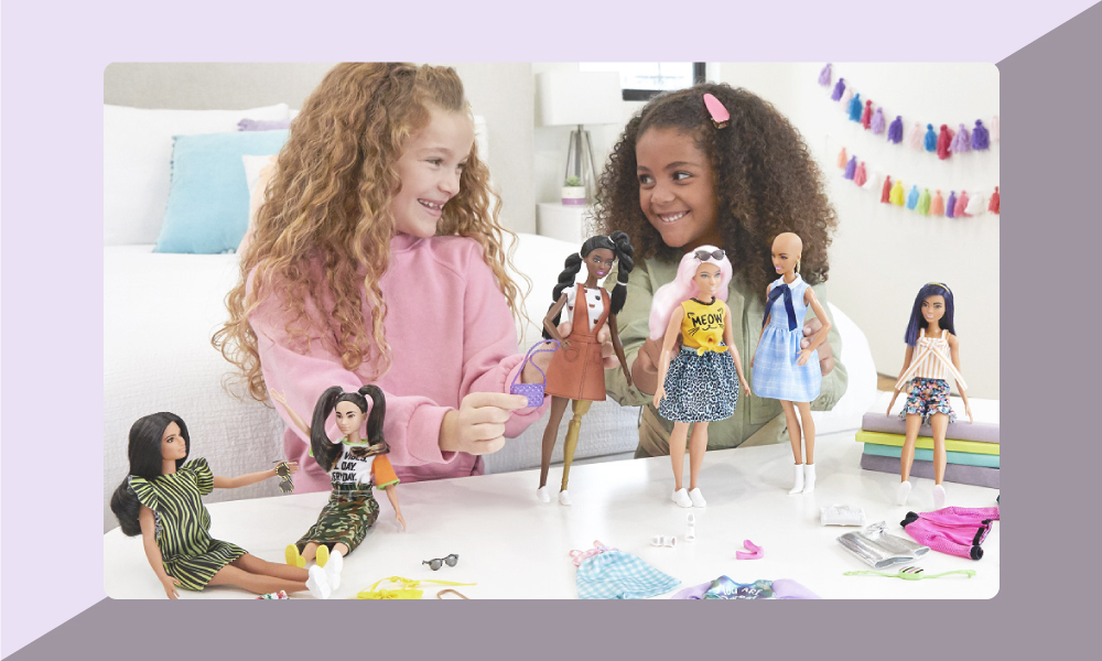 Image of two girls playing with Barbie dolls