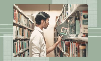 A young man picking up a Java book from a library