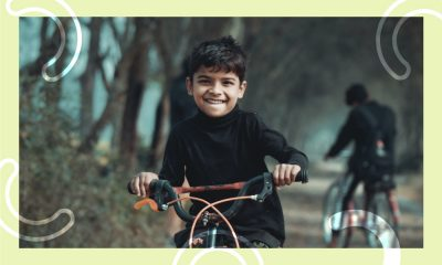 A child riding a bike on a forest road.