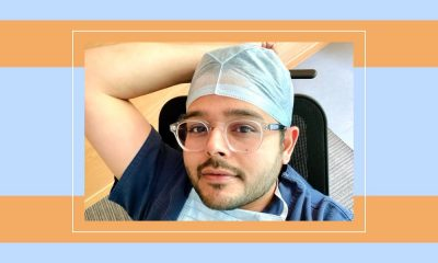 Dr. Munjaal Kapadia's selfie in his blue doctor scrubs. A mask hangs around the bespectacled gynaecologist. The photograph is on a striped, orange and blue backdrop