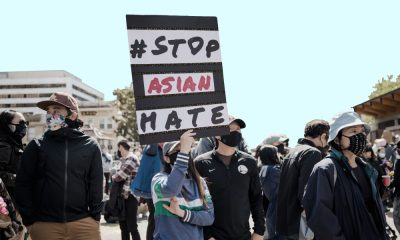"A woman holding a poster at a protest. the black poster, in protest of hate crimes against Asian Americans, simply says, ""#StopAsianHate""."