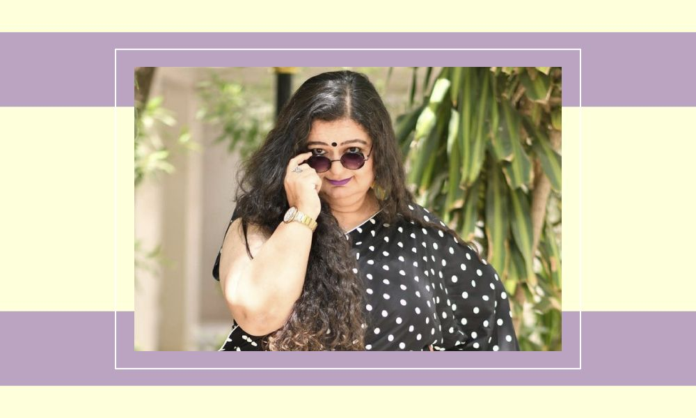 Photo of Dr. Falguni Vasavada in a black polka dotted sari, pulling her glasses down to her nose with her right hand