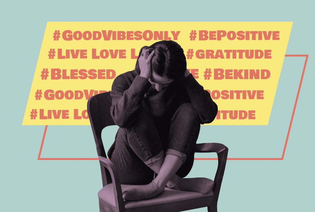 a black and white image of a woman holding her hands to her head sitting on a chair and behind are is a yellow and red speech bubble that says #goodvibesonly #bepositive #gratitude #livelovelaugh