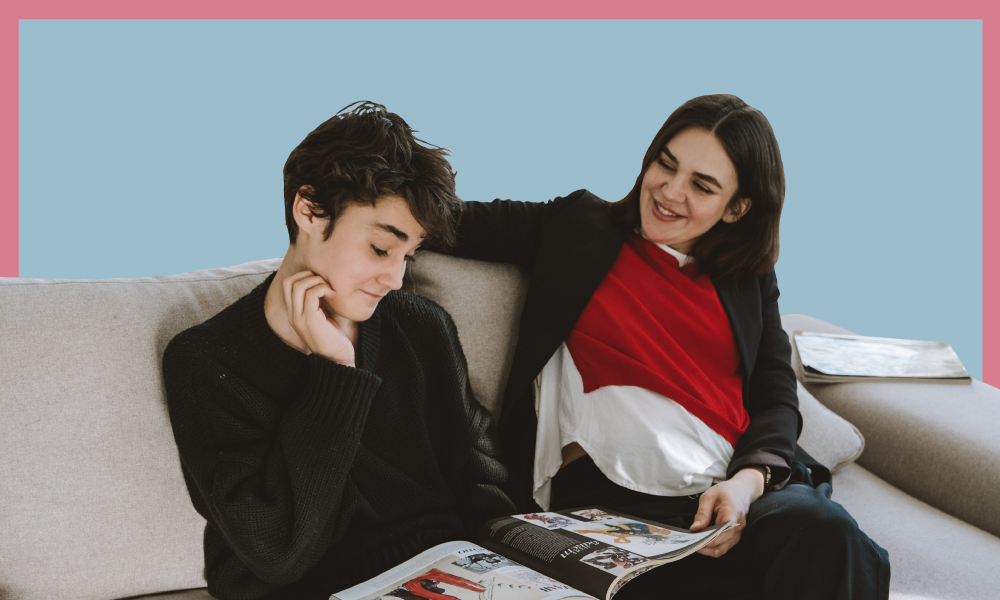 A woman talks to a teenage boy, with a book in his lap, while sitting on a couch.