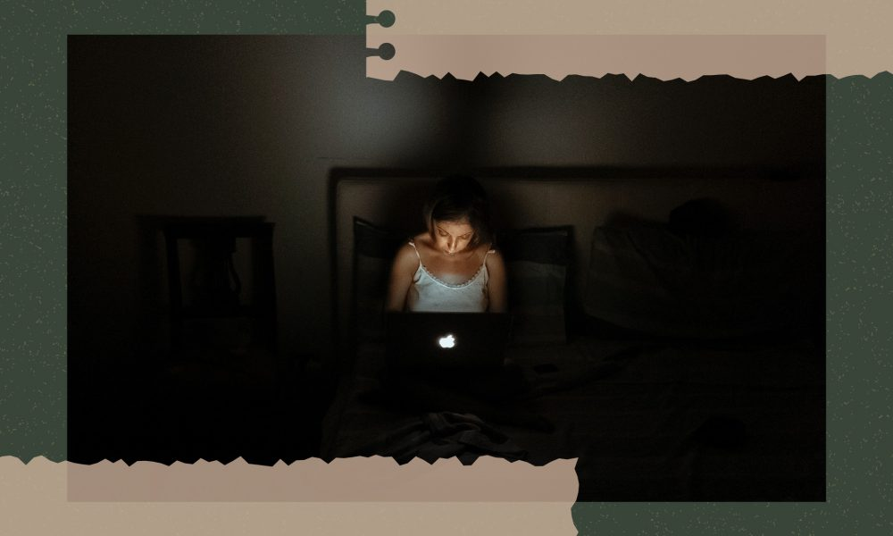 An image of a young woman sitting in the dark, working on her laptop, which is shining light on her